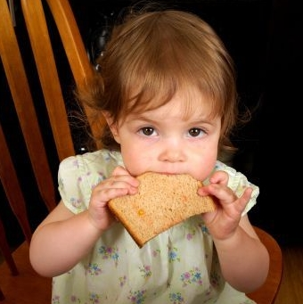 photo of child eating wheat bread