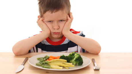 photo of child who doesn't want plate of vegetables