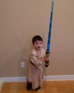 small child with light saber and Ben Kenobi costume